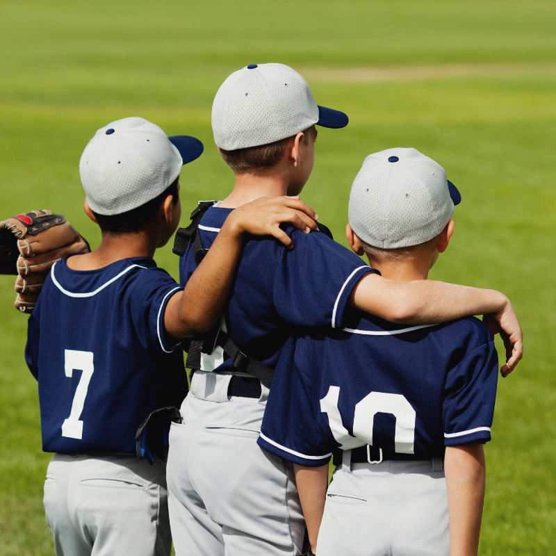Youth baseball players with arms around shoulders