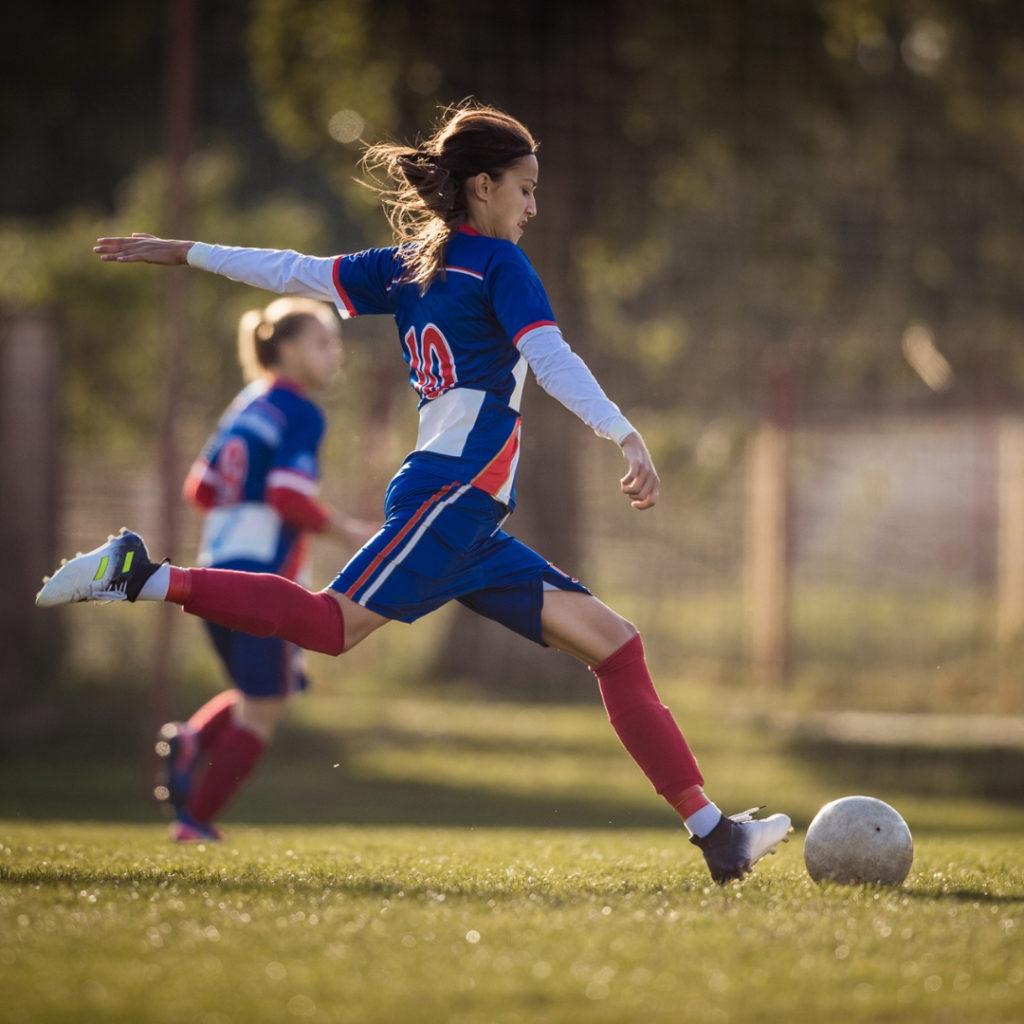 woman kicking soccer ball