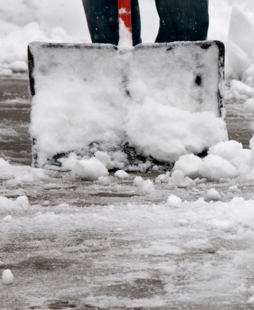 person shovelling snow to avoid concussion during winter
