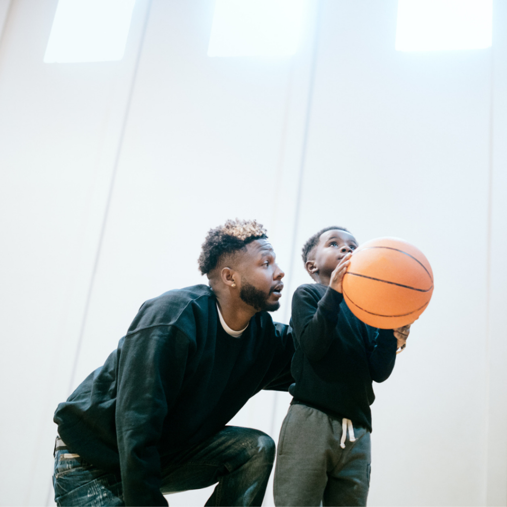 father helping son play basketball