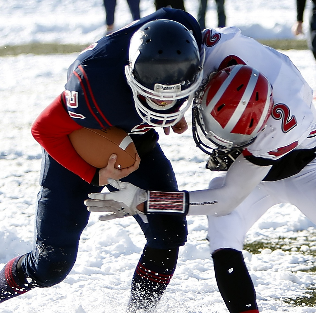 football players colliding on snowy field