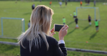 mother recording youth sports game on phone